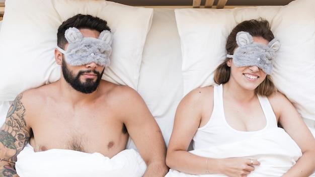 Vista de ángulo alto de pareja durmiendo en la cama con hilo de caramelo