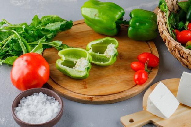 Vista de ángulo alto pimiento verde cortado por la mitad en la tabla de cortar con tomates, sal, queso, verduras en superficie gris