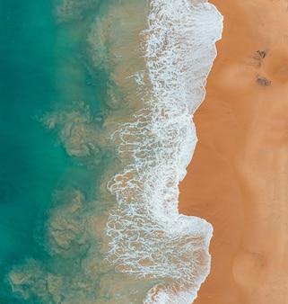 Vista de ángulo alto de la playa y el mar bajo la luz del sol: ideal para fondos y fondos de pantalla
