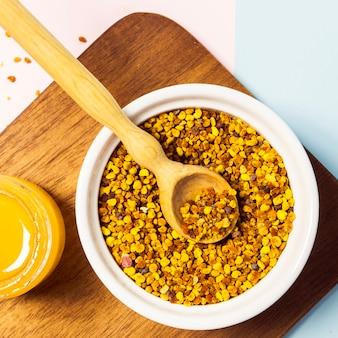 Vista de ángulo alto de polen de abeja y miel sobre tabla para cortar madera