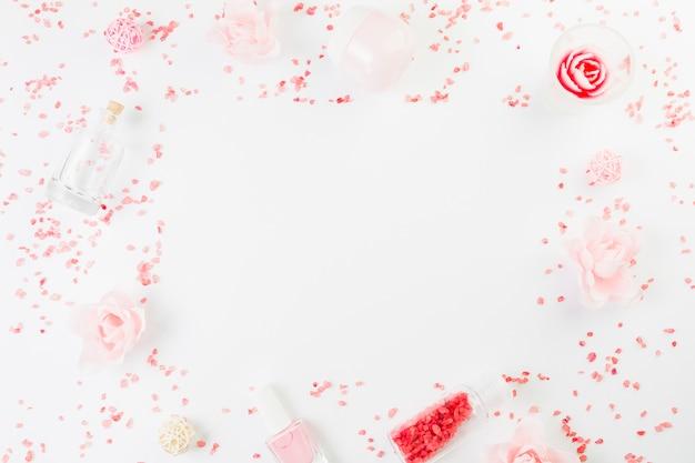 Vista de ángulo alto de productos de belleza formando marco sobre fondo blanco