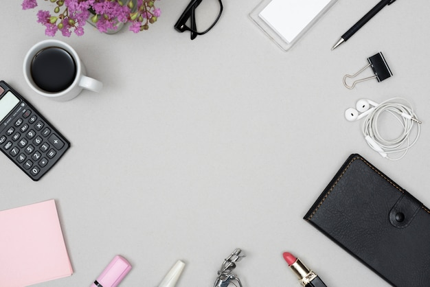 Vista de ángulo alto de productos cosméticos; material de oficina; taza de café; lente dispuesta sobre fondo gris