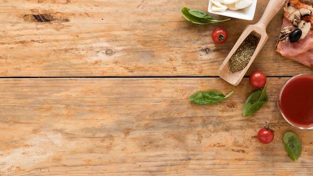 Vista de ángulo alto de rebanada de pizza; hierbas; tomate; hoja de albahaca; salsa de tomate con queso sobre fondo de madera