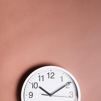Vista de ángulo alto de un reloj de alarma sobre fondo marrón