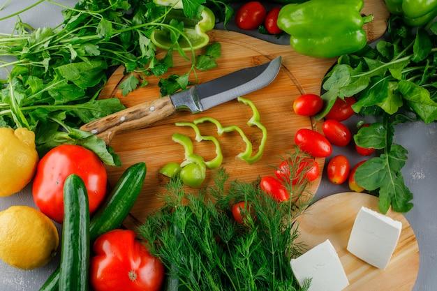 Vista de ángulo alto en rodajas de pimiento verde en la tabla de cortar con tomates, sal, queso, limón, verduras, cuchillo en superficie gris