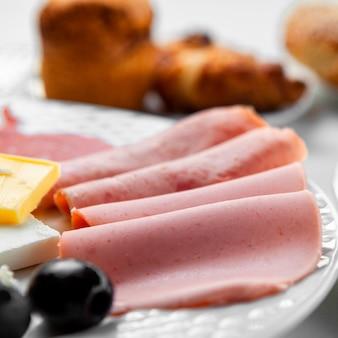 Vista de ángulo alto en rodajas de salchicha en placa, con pasteles en la mesa