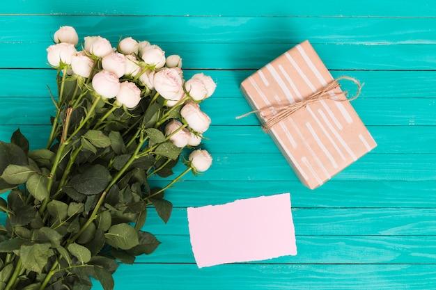 Vista de ángulo alto de rosas blancas; caja de regalo y papel en blanco sobre fondo verde.