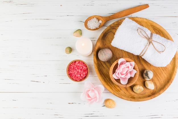 Vista de ángulo alto de sal; vela; piedras de spa; toalla y flor sobre fondo de madera