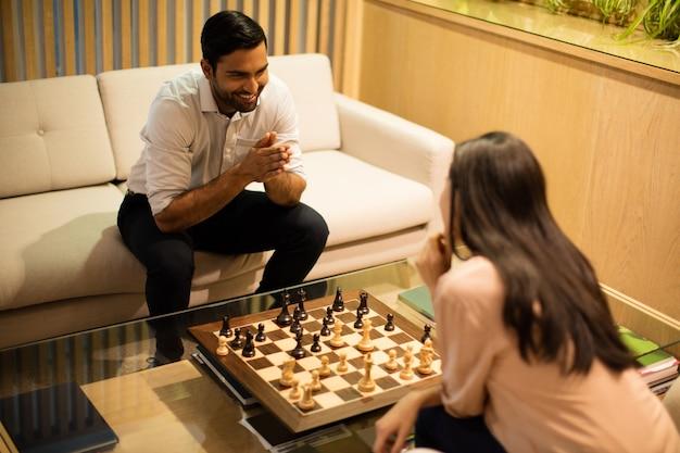 Vista de ángulo alto de sonrientes colegas de negocios jugando al ajedrez