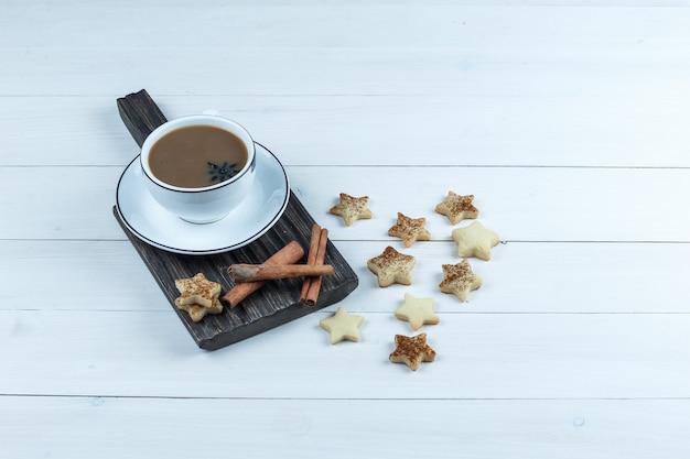 Vista de ángulo alto taza de café, canela en tabla de cortar con galletas estrella sobre fondo de tablero de madera blanca. horizontal