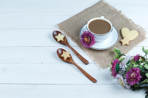 Vista de ángulo alto taza de café, galletas en forma de corazón y estrella en un pedazo de saco con flores, galletas en cucharas de madera sobre fondo de tablero de madera blanca. horizontal