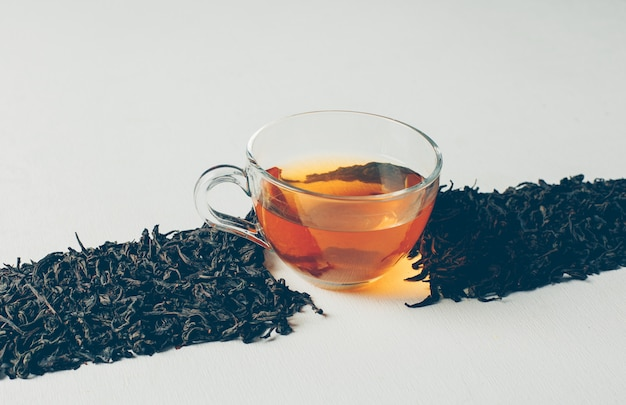 Vista de ángulo alto té negro en forma de línea con una taza de té