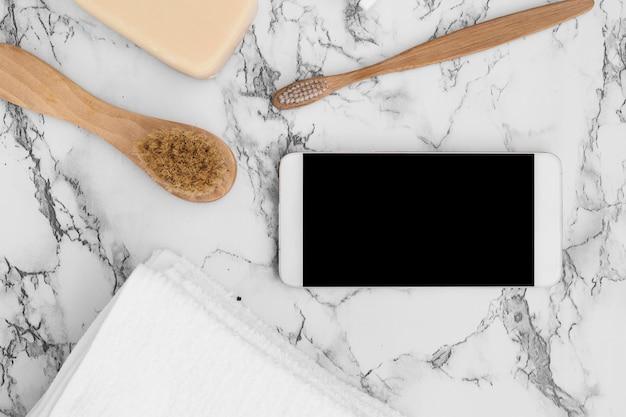 Vista de ángulo alto del teléfono móvil; jabón; toalla y cepillo sobre fondo de mármol