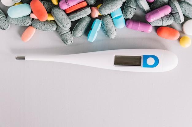 Vista de ángulo alto de termómetro y pastillas de colores sobre fondo blanco