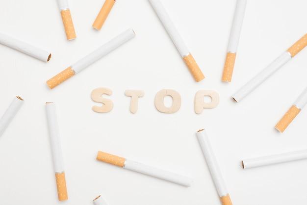 Vista de ángulo alto de texto de parada y cigarrillos sobre fondo blanco