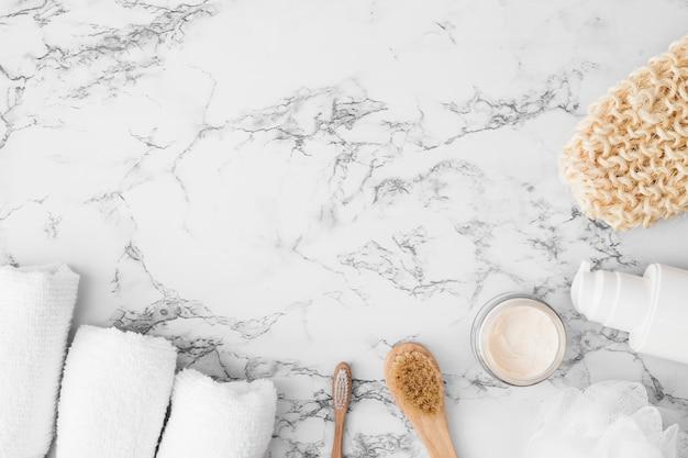 Vista de ángulo alto de toallas; cepillo; crema hidratante; esponja; botella cosmética y guante de fregado en superficie de mármol