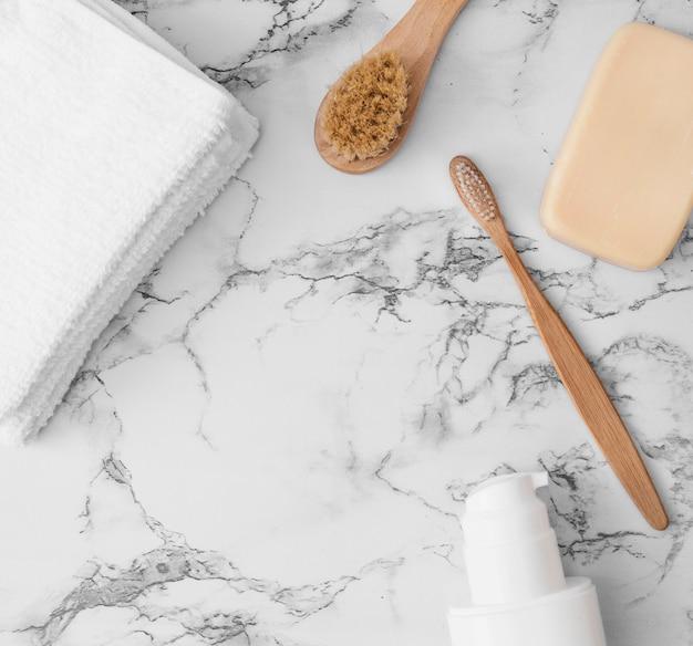 Vista de ángulo alto de toallas; cepillo; jabonera y botella cosmética en superficie de mármol.
