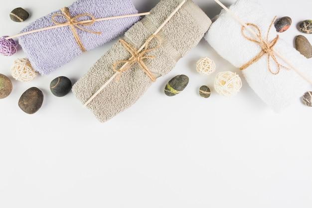 Vista de ángulo alto de toallas y piedras de spa sobre fondo blanco
