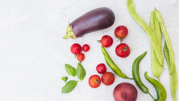 Vista de ángulo alto de tomates cherry; habas de jacinto; albahaca; cebolla y chiles verdes sobre fondo blanco
