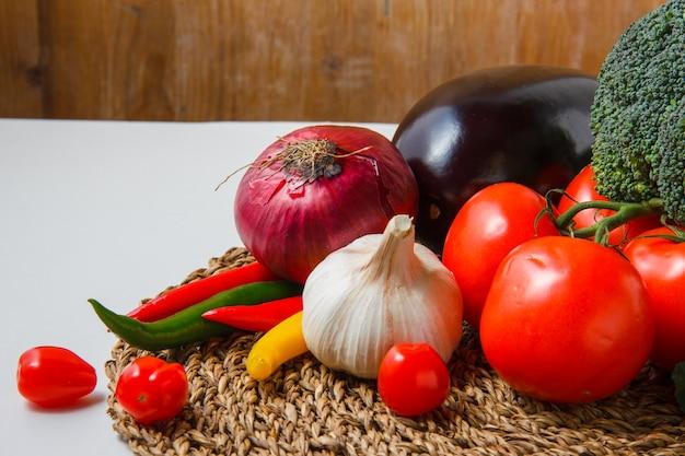 Vista de ángulo alto tomates con pimientos, cebolla, berenjena, pepino, brócoli, ajo en salvamanteles y superficie blanca. horizontal