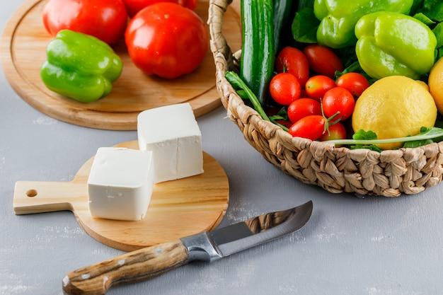 Vista de ángulo alto tomates en tabla de cortar con cuchillo, pimiento verde, limón, pepino, queso, verduras en superficie gris