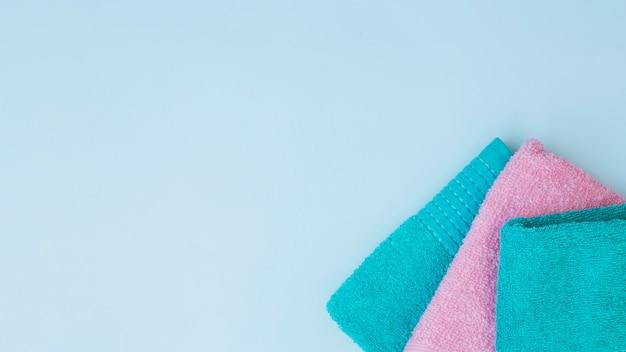 Vista de ángulo alto de tres toallas en el fondo azul