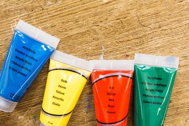 Vista de ángulo alto de tubo de colores líquidos en superficie de madera