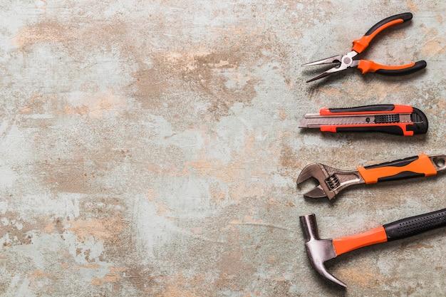 Vista de ángulo alto de varias herramientas de trabajo sobre fondo de madera vieja