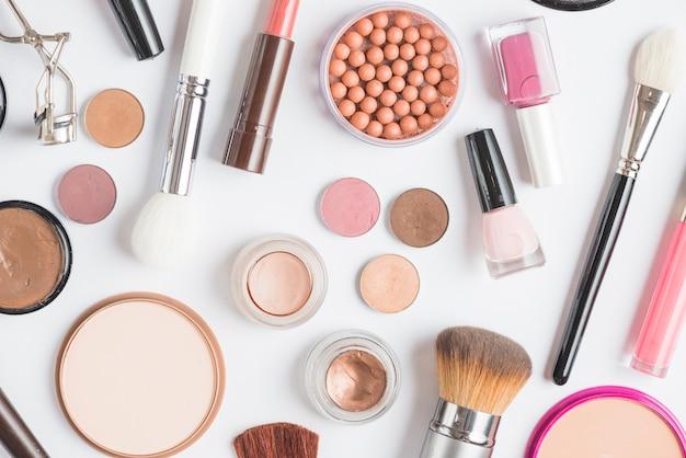 Vista de ángulo alto de varios productos de maquillaje sobre fondo blanco