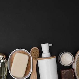 Vista de ángulo alto de varios productos de spa sobre fondo negro