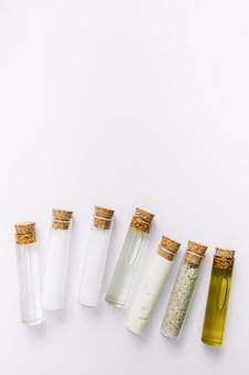 Vista de ángulo alto de varios tubos de ensayo cosméticos sobre fondo blanco