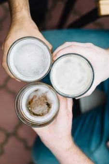 Vista de ángulo alto del vaso tostado de bebidas alcohólicas de un amigo masculino