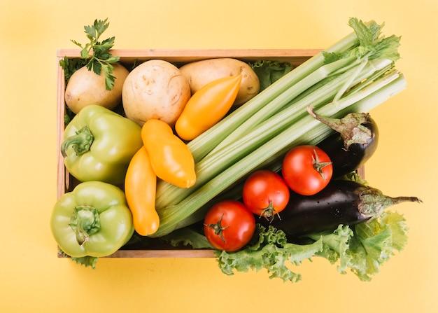 Vista de ángulo alto de verduras frescas en un recipiente sobre fondo amarillo