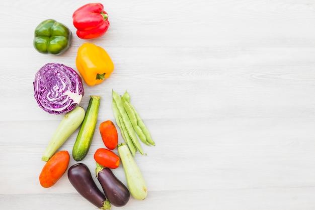 Vista de ángulo alto de verduras frescas sobre fondo de madera