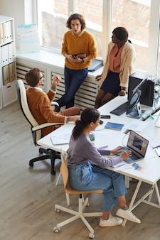 Vista de ángulo alto vertical en el equipo de desarrollo de ti multiétnico que colabora en un proyecto empresarial mientras trabaja en un estudio de producción de software