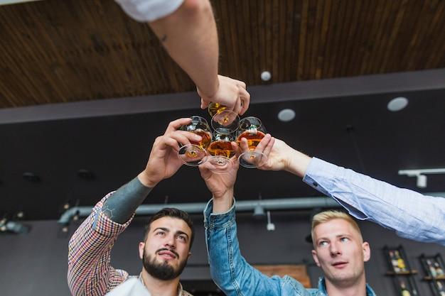 Vista de ángulo bajo de amigos varones levantando brindis en el restaurante