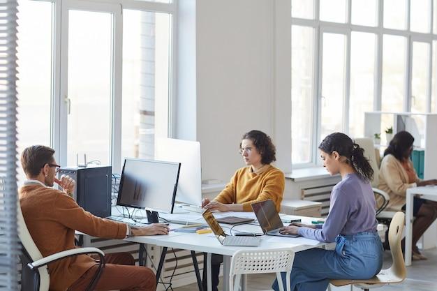 Vista de ángulo amplio en el equipo de desarrollo de software diverso que usa computadoras en el lugar de trabajo en el interior de la oficina blanca, espacio de copia
