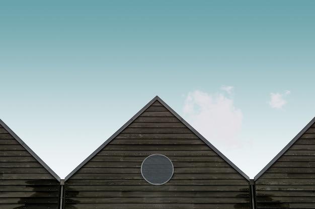Vista de ángulo bajo de las casas marrones de madera bajo el cielo azul