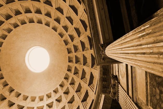 Vista de ángulo bajo la cúpula y el pilar de mármol del panteón roma italia