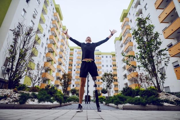 Vista de ángulo bajo de deportista guapo con pierna artificial de pie con las manos en el aire al aire libre rodeado de edificios.