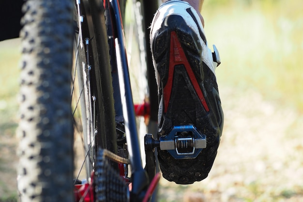 Vista de ángulo bajo detalle de los pies del hombre ciclista en bicicleta de montaña al aire libre. sendero en camino rural. solo las piernas son visibles.