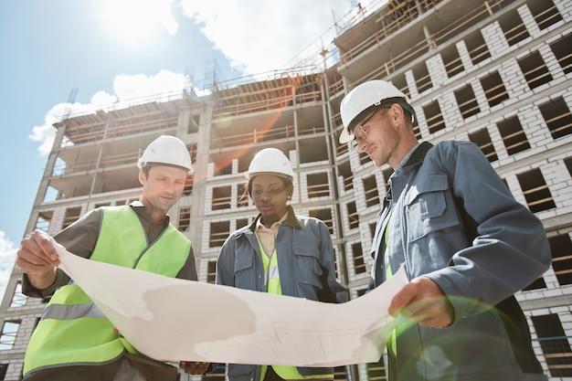 Vista de ángulo bajo en diverso grupo de ingenieros discutiendo planos de planta en el sitio de construcción