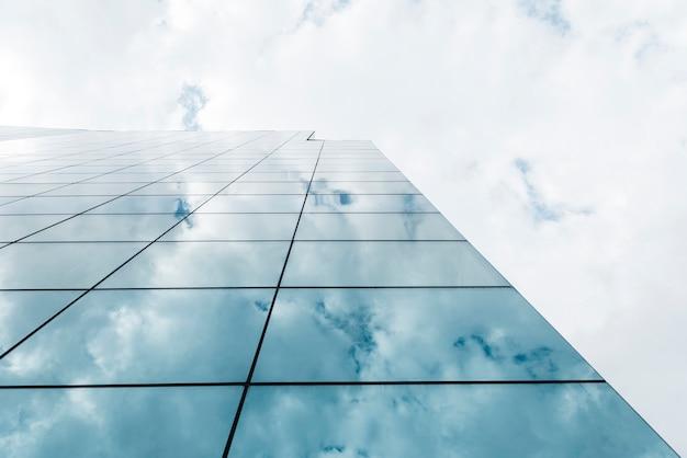 Vista de ángulo bajo edificio alto y nubes