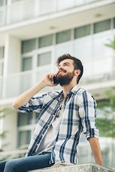 Vista de ángulo bajo de hipster barbudo hablando por teléfono fuera del edificio