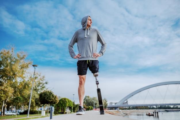 Vista de ángulo bajo de hombre discapacitado caucásico deportivo en ropa deportiva y con pierna artificial de pie con las manos en las caderas en la pista de carreras junto al río y mirando a otro lado.