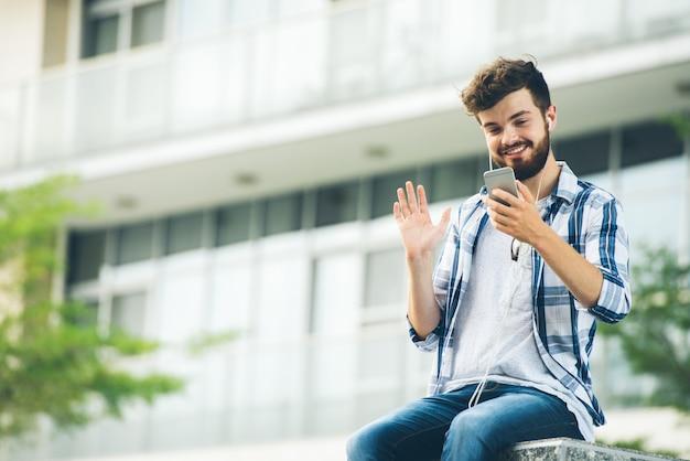 Vista de ángulo bajo del hombre llamando por video a un amigo sentado en el campus universitario
