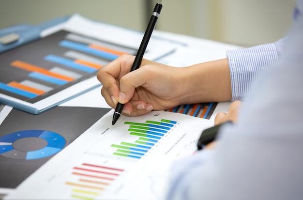 Vista de ángulo lateral de gente de negocios escribiendo sobre papeleo en la mesa