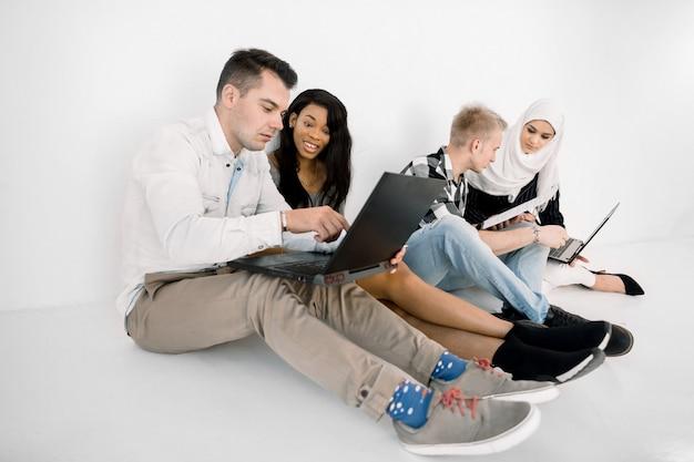 Vista de ángulo lateral del grupo diverso de cuatro personas multiétnicas, trabajando o estudiando juntas, usando computadoras portátiles y tabletas