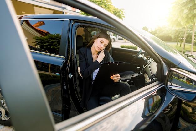 Vista de ángulo lateral de la joven y bella empresaria, sentada dentro de su automóvil en el asiento del pasajero, mientras usa una tableta digital y habla por teléfono móvil
