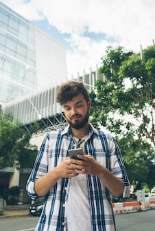 Vista de ángulo bajo de mensajes de texto de chico hipster en un teléfono inteligente en medio de la calle